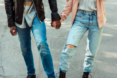 Photo for Cropped image of couple in stylish shoes and jeans standing together on one longboard and holding hands - Royalty Free Image