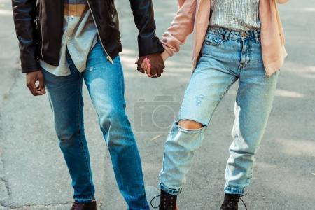 Photo pour Cropped image de couple dans des chaussures élégantes et jeans debout ensemble sur un longboard et main dans la main - image libre de droit