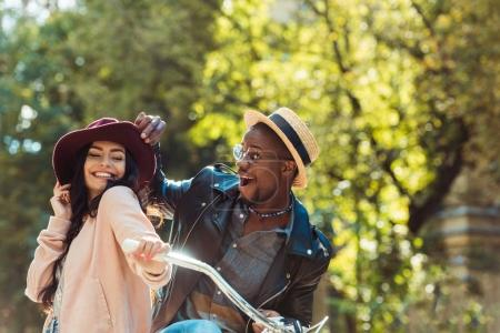 Photo for Affectionate interracial couple laughing and standing together with a bicycle - Royalty Free Image