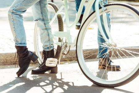 Man and woman standing with one bike