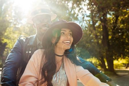 Photo for Beautiful interracial couple walking in a park in a sunny day - Royalty Free Image