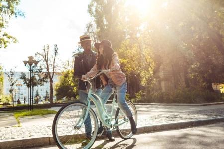 Boyfriend helping girlfriend riding bike