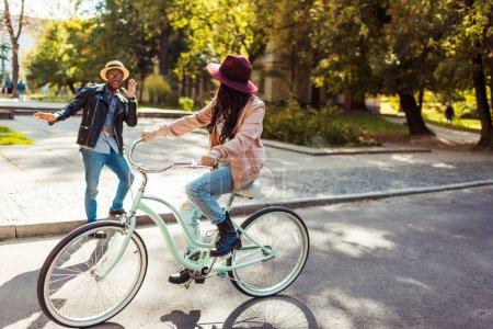 Girlfriend riding bike and boyfriend grimacing