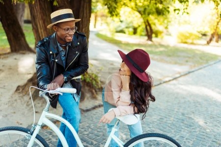 Photo for Lovely interracial couple standing and leaning on a bike - Royalty Free Image