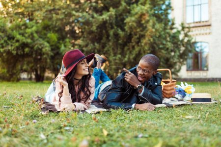 Multicultural couple lying on blanket in park