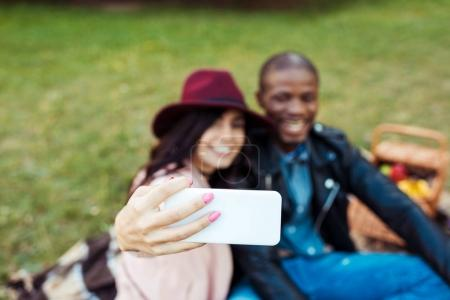 multicultural couple taking selfie