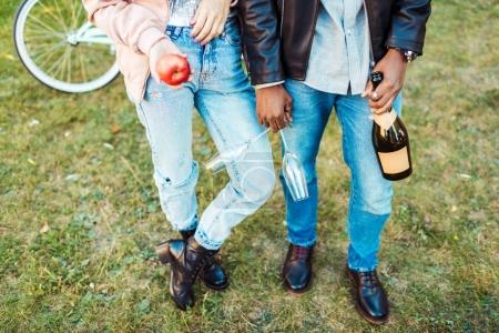Couple standing with apple, glasses and champagne
