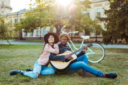 Photo pour Charmant couple interracial assis avec une guitare dans le parc - image libre de droit