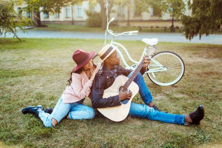 Photo for Boyfriend playing the guitar for his girlfriend at the picnic - Royalty Free Image