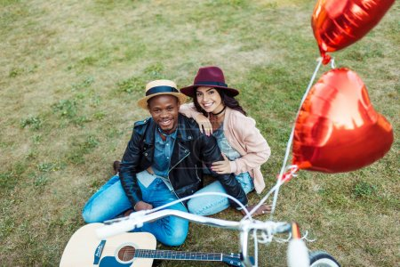 Photo for Interracial couple sitting on a grass with bicycle, guitar and red balloons on foreground - Royalty Free Image