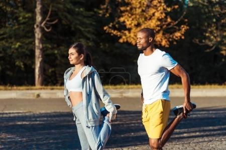 Photo for Interracial couple stretching legs on a road at the park - Royalty Free Image