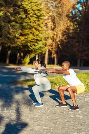 couple squatting in park