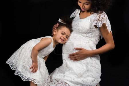 daughter listening pregnant mothers belly