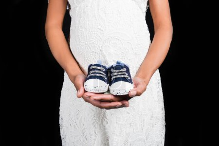 Pregnant woman holding small shoes