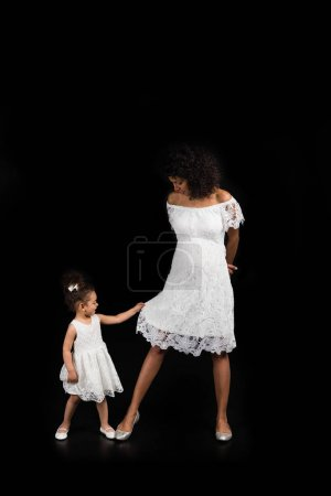 Small daughter playing with mothers dress