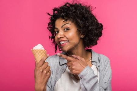 Photo for Young African american woman showing at ice cream and smiling isolated on pink - Royalty Free Image