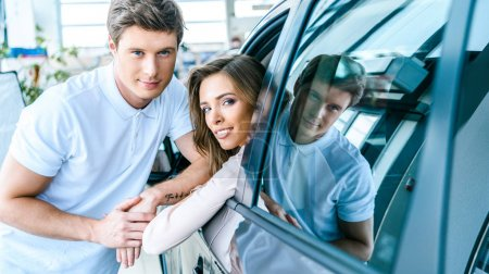 Woman in car and man standing near