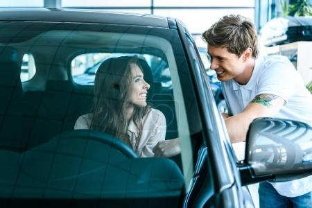 Man talking to woman sitting in car