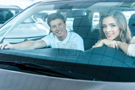 Couple sitting in car in showroom