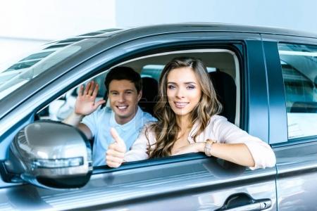 Photo pour Petit ami agitant la main, petite amie montrant pouce vers le haut assis dans une nouvelle voiture dans le showroom - image libre de droit