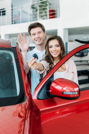 Photo for Boyfriend waving a hand, girlfriend showing key from new car in showroom - Royalty Free Image
