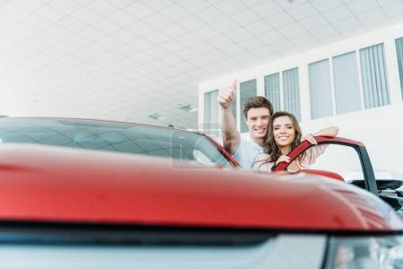 Man showing thumb up to car
