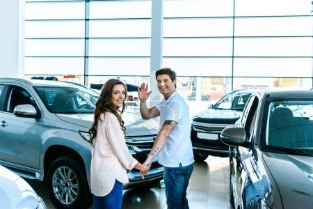 Man waving hand in car showroom