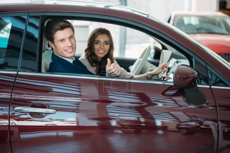 Photo for Manager showing thumb up to car while sitting in a car with customer - Royalty Free Image