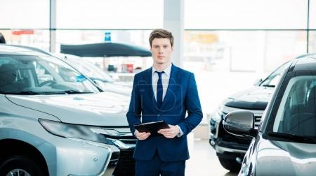Photo pour Beau gestionnaire permanent entre les voitures dans la salle d'exposition et regardant la caméra - image libre de droit