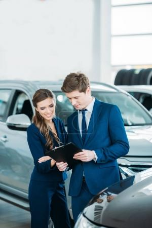 Photo for Female and male Sales managers of a car showroom standing and looking at clipboard - Royalty Free Image