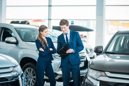 Photo for Sales managers of a car showroom standing and looking at clipboard - Royalty Free Image