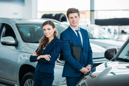 Photo for Female and male Sales managers of a car showroom standing and looking at the camera - Royalty Free Image