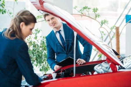 Photo pour Responsables des ventes féminines et masculines d'une salle d'exposition de voiture regardant sous le capot ouvert - image libre de droit