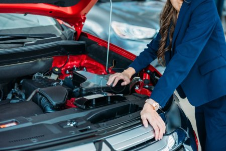 Manager looking under car hood
