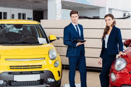 Photo for Sales managers posing in a car showroom and looking at camera - Royalty Free Image