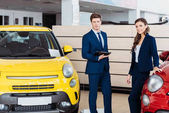 Sales managers posing in car showroom