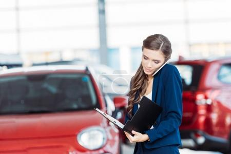 Photo for Female manager of car showroom talking by smartphone and looking into clipboard folder - Royalty Free Image