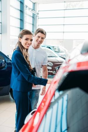 sales manager showing car to customer
