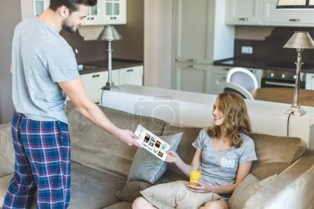 man showing tablet to his girlfriend