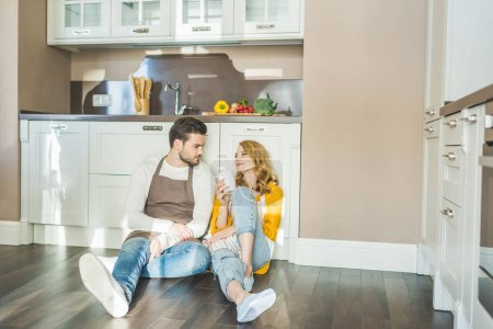 Photo for Attractive young couple sitting on kitchen floor at home - Royalty Free Image