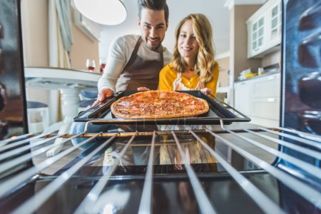 Photo for Young couple taking burnt pizza from stove - Royalty Free Image