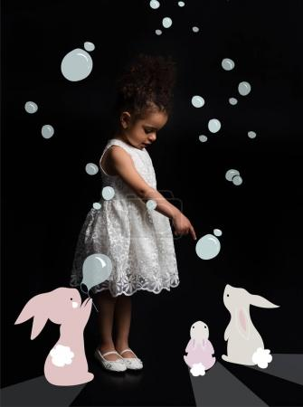 Photo for Preschooler kid in white dress blowing bubbles with funny colorful bunnies isolated on black - Royalty Free Image