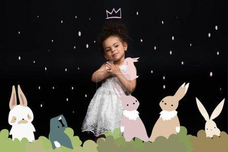 Foto de Permanente princesa de niños de preescolar en vestido blanco con divertidos conejitos colores aislados en negro - Imagen libre de derechos