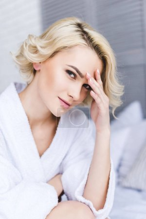 Photo for Close-up portrait of beautiful blonde woman in bathrobe looking at camera - Royalty Free Image