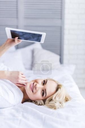 Photo pour Jolie fille blonde tenant une tablette numérique avec écran blanc et souriant à la caméra dans la chambre à coucher - image libre de droit