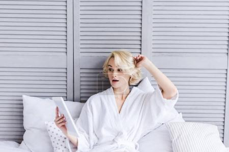 beautiful surprised girl in bathrobe using digital tablet on bed