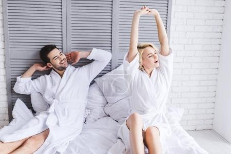 Photo for Young couple in bathrobes stretching at morning in bed - Royalty Free Image