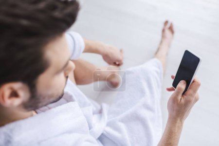Photo for Selective focus of bearded man in bathrobe using smartphone with blank screen - Royalty Free Image