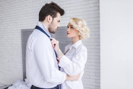 young couple looking at each other while woman taking off necktie of boyfriend