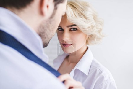 young woman looking at camera while taking off necktie of boyfriend